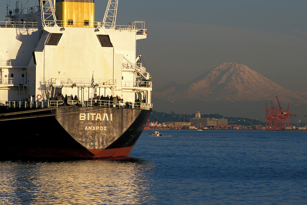USA, Washington, Seattle, Cargo ship docked at Pier 86 grain terminal with Mount Rainier in distance at sunset