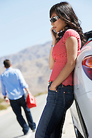 Woman using mobile phone leaning on out of gas car on desert roadside