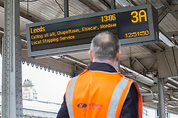 © Licensed to London News Pictures . FILE PICTURE DATED 26/02/2015 of a railway worker looking at a departure board for Leeds on the platform at Sheffield Train station as the government has today ( 25th June 2015 ) announced the cancellation of several major rail upgrade across the north of England . Photo credit : Joel Goodman/LNP