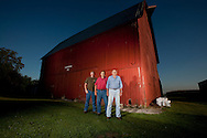 Sean Riordan(L), stands with his father, John and grandfather Dale, in front of their historic Barn built by his great-grandfather Clem on their family farm on August 11, 2008 in Reddick, Illinois.