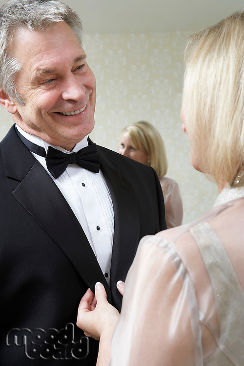 Middle-aged woman buttoning husband's tuxedo jacket