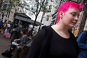 A woman with pink dyed hair walk through a London street.