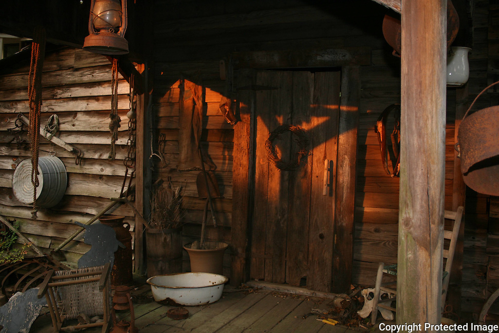 The front doorway to a rustic, backwoods country home with antiques, farm equipment and other interesting implements and objects.