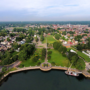 An aerial view of Prescott Park's waterfront on the Piscataqua River. Strawbery Banke Museum and downtown Portsmouth surround the park to the rear, and the gundalow Piscataqua (masted ship) sits docked in front of the park.