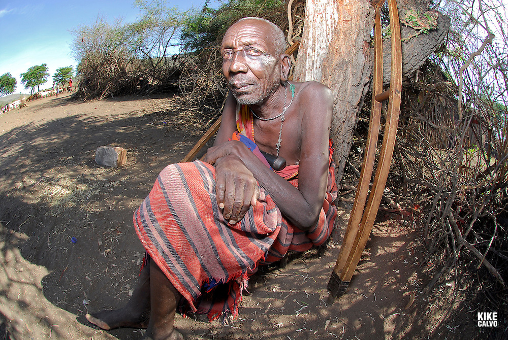 Elder man resting on a tree log, with his wooden crutches nearby. Masai Mara tribe around the Masai Mara National Park. Kenya. East Africa.
