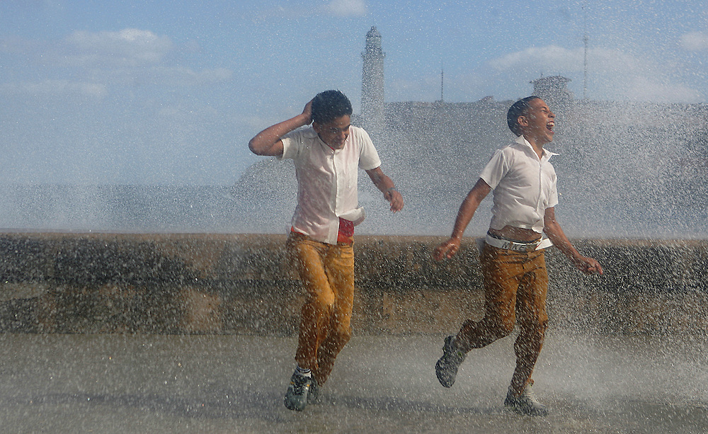 Two school boys shriek with laughter after a rogue waves hits the Malecon sea wall and drenches them, Havana Cuba.Morro castle is viewed in the background.<br />