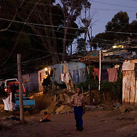 A man walks through the gloaming as night falls on Imizamo Yethu shanty town, Hout Bay, Cape Town, South Africa. The work of the CPF and neighbourhood watch have seen the crime rate in Hout Bay drop 63%, but relations between the shanty town of Imizamo Yethu and Hout Bay are tense.  photo  Leonie Marinovich