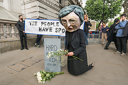 June 9, 2017 - London, UK - London, UK. 9th June 2017. After election results showed that no party had a majority, protesters came to Westminster to demand that Theresa May resign. She is intending to stay on and try and govern, relying on votes from the Ulster protestant extremist DUP party, linked to loyalist paramilitaries. Avaaz brought a person with a large caricature head Of Theresa May to Downing St to pose in front of a banner 'The People Have Spoken' and lay white roses in front of a gravestone with the message 'Hard Brexist R.I.P 2016-2017'. Peter Marshall Images Live (Credit Image: © Peter Marshall/ImagesLive via ZUMA Wire)