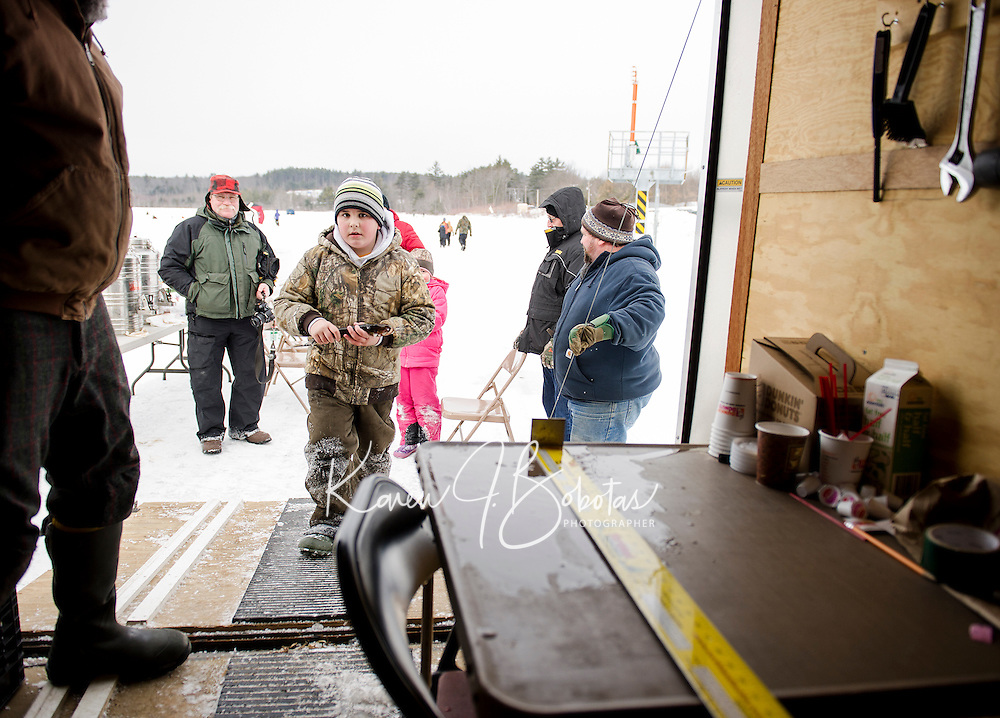 Caden Stone carries brings his catch in to Mark Jensen to be measured during Belknap County Sportmen's Club Ice Fishing event on Sunday morning.  (Karen Bobotas/for the Laconia Daily Sun)