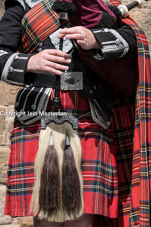 Detail of man playing bagpipes wearing traditional military uniform with tartan and kilt in Edinburgh, Scotland, united Kingdom