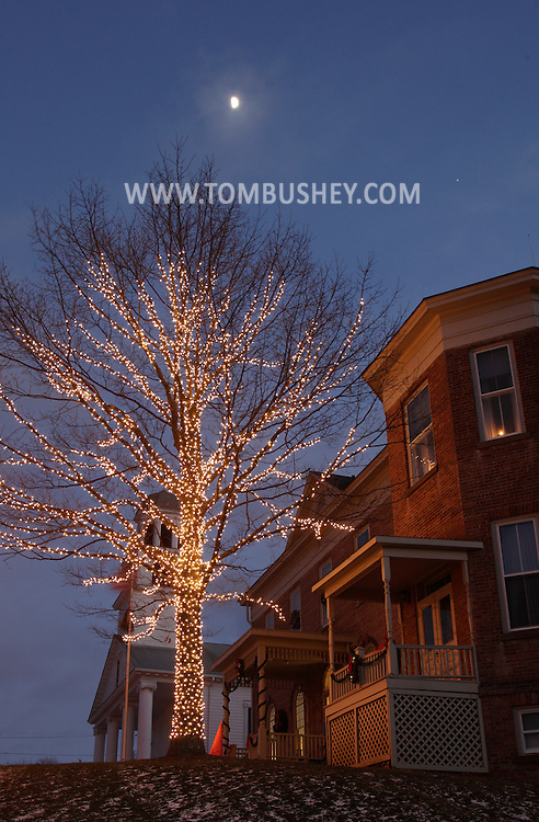 Montgomery, New York - A tree is decorated with holiday lights in front of the Montgomery Village Hall and  library on  Dec. 14, 2010. The brick structure, built in 1818, was originally the Montgomery Academy. The First Presbyterian Church is in the background.