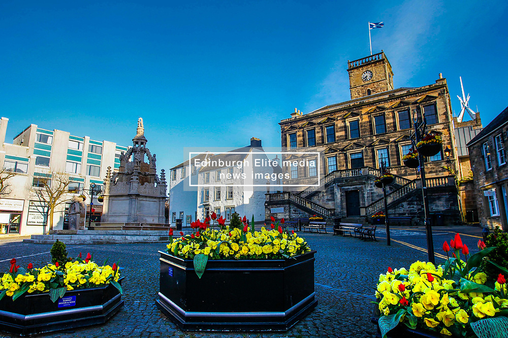 Pictured: Easter Sunshine falls on the ancient Cross Well and Town Hall in the centre of Linlithgow complete with a display of Easter flowers . Linlithgow is a royal burgh in West Lothian, Scotland. It is West Lothian's county town. <br /> The chief historic attraction of Linlithgow is the remains of Linlithgow Palace, the birthplace of James V and Mary, Queen of Scots. The Cross Well has just undergone a full refurbishment to restore it to its former glory. <br /> <br /> <br /> Andrew West/ EEm