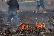 The feet of people walking across the burning embers of a large bonfire during the Hi Watari firewalking festival, Takaosan guchi near Tokyo, Japan. Sunday March 8th 2009
