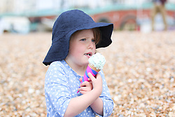 © Licensed to London News Pictures. 25/05/2015. Brighton, UK. Amanda Northcote-Green and 4.5 year old Poppy enjoy an Ice cream. Thousands of people take to the beach in Brighton on the May Bank Holiday Monday, today May 25th 2015. Photo credit : Hugo Michiels/LNP