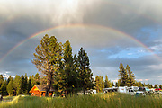 BC00631-00...BRITISH COLUMBIA - Rainbow over campground at Kikomun Provincal park.