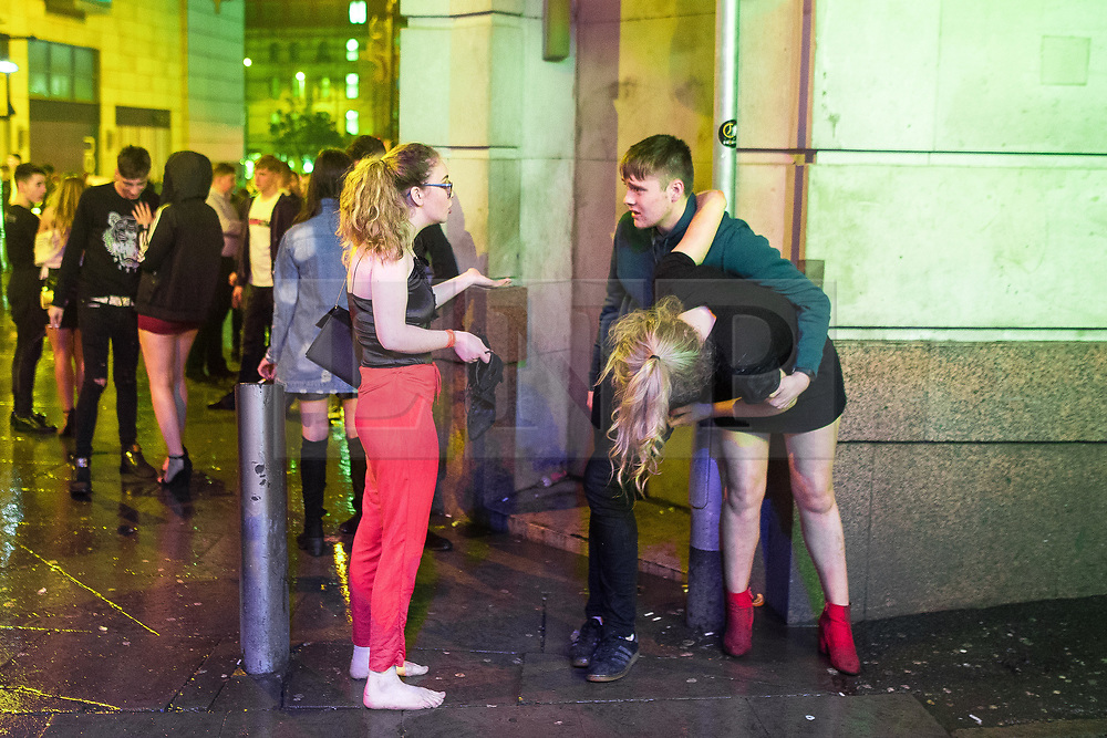 """© Licensed to London News Pictures . 23/12/2017. Manchester, UK. A man supports a woman against a wall outside the Printworks in Manchester City Centre overnight during """" Mad Friday """" , named for being one of the busiest nights of the year for the emergency services in the UK . Photo credit: Joel Goodman/LNP"""