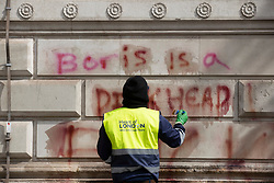 © Licensed to London News Pictures. 07/06/2020. London, UK. The spray painted words 'Boris is a dickhead' are painted with a cleaning solution before being power washed off the walls of The Foreign Office in Whitehall after yesterday's Black Lives Matter protest march . New quarantine rules on passengers entering the United Kingsom come into force tomorrow. People entering the country will have to quarantine for two weeks. Photo credit: Peter Macdiarmid/LNP