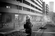 Germany, Frankfurt am Main : a woman walks past a burning barricade during a demonstration organized by the Blockupy movement to protest against the policies of the European Central Bank (ECB) on March 18, 2015. The Ecb inaugurated today its new headquarter.<br /> <br /> .