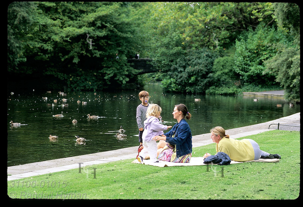 Family relaxes on blanket on banks of duck pond at St. Stephen's Green on a September afternoon; Dublin, Ireland.