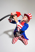 Uncle Sam kneeling on the ground as he sucks gasoline from a gas nozzle..Model Release: 20080626_MR_A