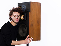 studio portrait of a one caucasian young man listening to music lover with speakerphones isolated on white background