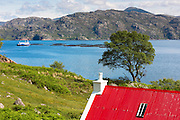 Salmon farm at Loch Torridon and cottage with red corrugated iron roof in Wester Ross in the Scottish Highlands