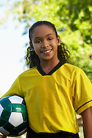 Girl (7-9 years) holding soccer ball under arm, portrait