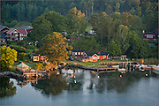 Pleasure boats and summer cottages by Bammarboda,  a seaside town on the Swedish coast seen from the sea on a cruise through the Stockholm Archipelago, a popular summer vacation and recreation area in Sweden.