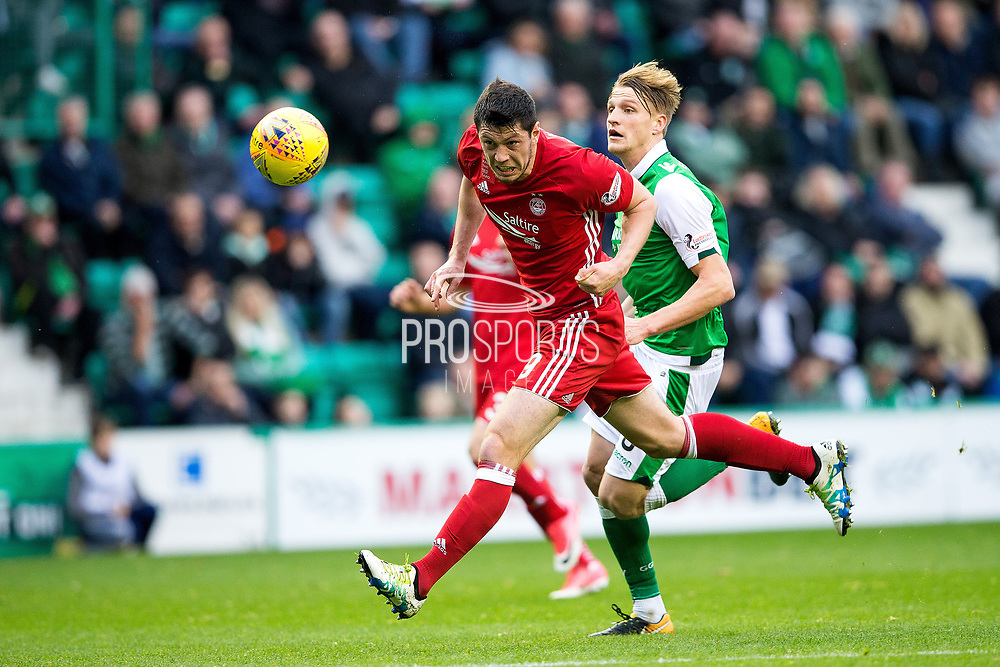 Aberdeen defender Scott McKenna (#19) heads the ball back to his goal keeper under pressure from Hibernian midfielder Vykintas Slivka (#8) during the Ladbrokes Scottish Premiership match between Hibernian and Aberdeen at Easter Road, Edinburgh, Scotland on 14 October 2017. Photo by Craig Doyle.