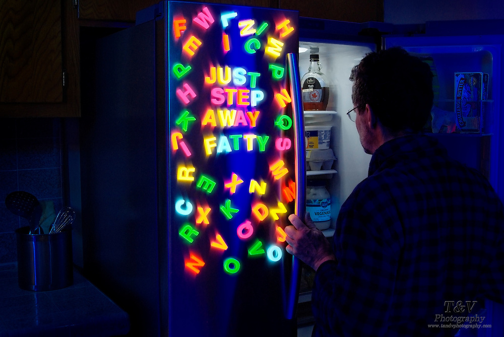"A man looks inside of a refrigerator door covered with glowing letters that read ""just step away fatty"".Black light"