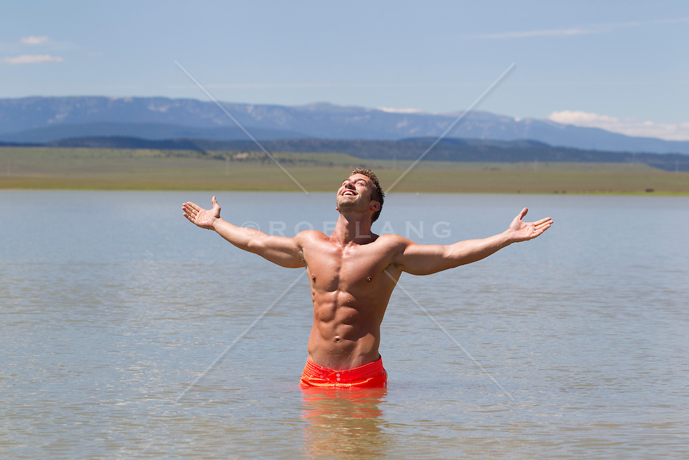 good looking shirtless man with a big smile and open arms while standing in a beautiful lake in New Mexico