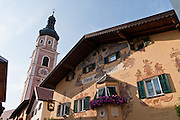 The church bell tower rises above Hotel Zum Wolf / al Lupo / Ulbergo Hotel, in Kastelruth / Castelrotto, a comune in Südtirol/South Tyrol/Alto Adige, in the Dolomites, Italy, near Bolzano and Seiser Alm (Alpe di Siusi). After Austria lost World War I, its South Tirol (Südtirol) became Italy's Alto Adige. German is the most spoken language in Kastelruth. The Dolomites were declared a natural World Heritage Site (2009) by UNESCO.