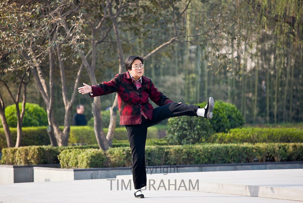 Woman practises Tai chi as part of her morning exercise in the park by the City Wall of Xian, China