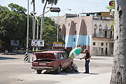 A broken-down Lada car is worked on my a mechanic in the street in Havana, Cuba