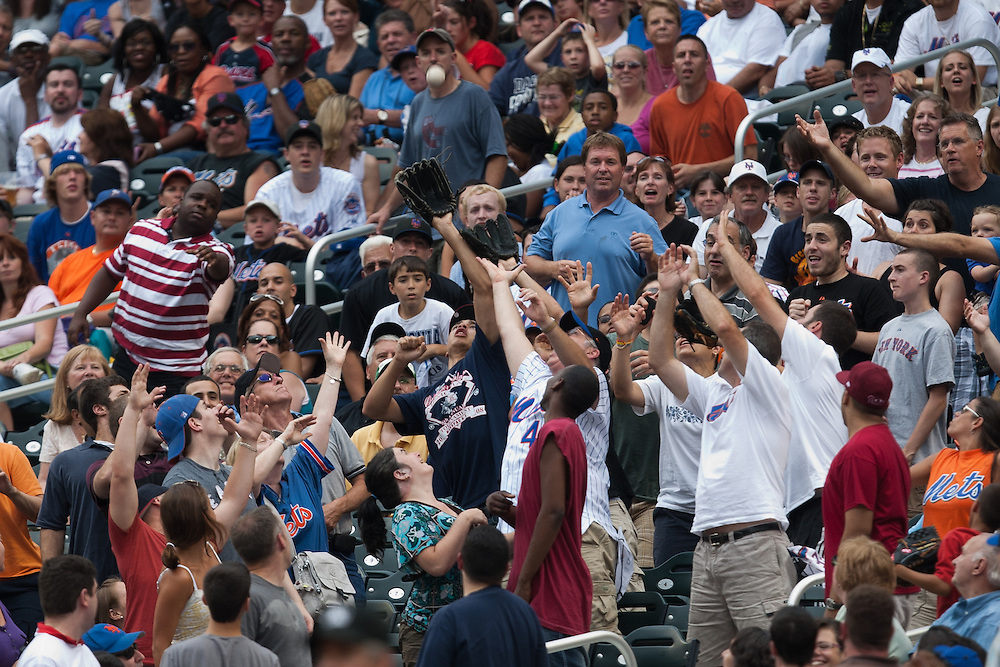 NEW YORK - JULY 10: Fans attempt to catch a foul ball during the game of the Atlanta Braves against the New York Mets at Citi Field on July 10, 2010 in the Queens borough of New York City. The Braves defeated the Mets 4 to 0. (Photo By: Rob Tringali) *** Local Caption ***