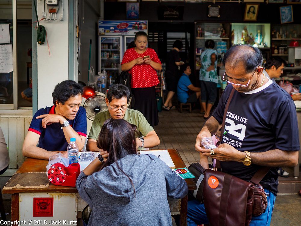 21 DECEMBER 2018 - CHANTABURI, THAILAND: Gem merchants in the gem market in Chantaburi. The gem market in Chantaburi, a provincial town in eastern Thailand, is open on weekends. Chantaburi used to be an active gem mining area in Thailand, but the mines are played out now. Now buyers and sellers come from around the world to Chantaburi for the weekend market. Many of the stones come from Myanmar, others come from mines in Afghanistan and Africa.       PHOTO BY JACK KURTZ