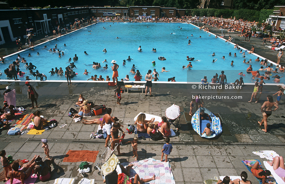 During an August heatwave, the population of Brixton and many others from all over London, bask in the glorious weather at the Brockwell (Brixton)  Lido in Brockwell Park, Herne Hill, South London. The Lido is a magnet for families, select groups, the young and old and represents an amalgam of humanity who enjoy the benefits of outdoor bathing and the friendship of meeting old friends and new acquaitances. We see a mass of people in late afternoon light with deep tans from the extended hot summer. Swimmers are in the unheated water, others jump in or stand on the edge thinking about their next dive. It is a scene of chaotic fun for all ages and backgrounds. Brockwell Lido is a large, open air swimming pool in Brockwell Park, Herne Hill, London. It opened in July 1937, closed in 1990 and after a local campaign was re-opened in 1994. Brockwell Lido was designed by HA Rowbotham and TL Smithson of the London County Council's Parks Department to replace Brockwell Park bathing pond. It is now a Grade II listed building