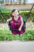 young girl of 3 on a swing in a playground