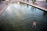 A boy plays in a pool in the Parque de Renacimiento, or Rebirth Park, in downtown Bogotá on Thursday, September 28, 2006. The park used to be part of Bogotá's Central Cemetery, but over the past few years the graves were moved and the area was turned into a park as part of Bogotá's ongoing process of revitalization. (Photo/Scott Dalton).