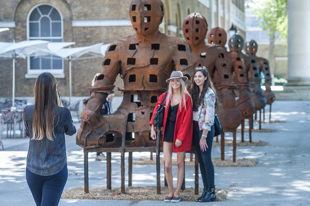 London, UK - 2 September 2014: visitors pose for pictures next to  Xavier Mascaró's  installation 'Guardians'. These rusted iron warriors, nearly 10 feet high, are both imposing and placid, and are inspired by medieval armour and ancient Egyptian and Greek art. Xavier Mascaró's first UK solo exhibition will run from 3 September until 5 October at Saatchi Gallery.