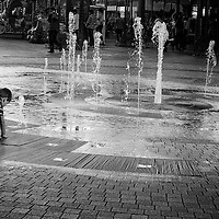 A child fascinated by the streams form the dancing water fountain.