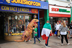 3 June 2017 - UEFA Champions League Final - Juventus v Real Madrid - A child fights a dinosaur outside awoke shop as Juventus fans look on - Photo: Marc Atkins / Offside.