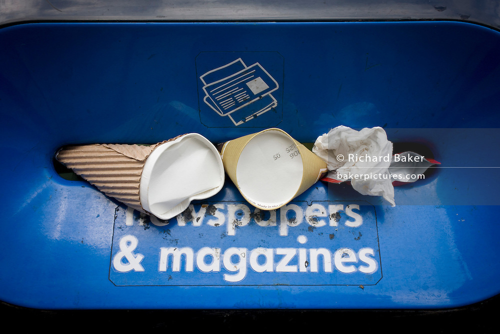 Instead of the intended newspapers and magazines, passers-by have instead stuffed coffee cups and general paper into a recycling bin slot in the City of London. The receptacle specifically states what should be inserted, but this has been ignored, its purpose disregarded for miscellaneous waste. On the top is also says that no tissues or cups are to be placed inside.