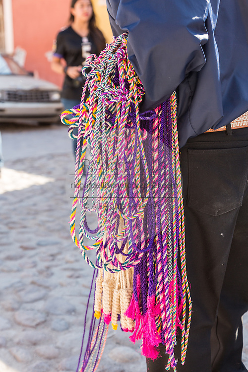 A Mexican man sells rope whips to religious pilgrims and penitents outside the Sanctuary of Atotonilco, and important Catholic shrine in Atotonilco, Mexico.