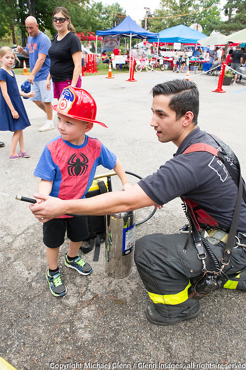 19 Sep 2015 Staten Island, New York US // FF Dominic Ventlora E154 helps Michael spray water from the can at the 8th annual Lt. John Martinson Memorial Picnic at the Hillside Swim Club //  Michael Glenn  /   for the FDNY