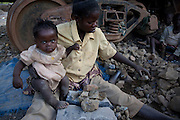 Kipushi, DRC. March 2009. Grandmothers, mothers and children spend their entire days on the discarded mine dumps, carrying out the most menial of manual labour. They progressively break up chunks of rocks into smaller and smaller pieces that will then be sold as building material. This might be the only way of life some of these children will ever know.