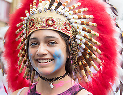 London, August 28th 2016. A young woman in a feathered head dress smiles for the camera as Europe's biggest street party, the Notting Hill Carnival gets underway.