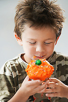 Young boy eating cupcake half length