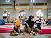 "08 FEBRUARY 2015  BANGKOK, THAILAND:  A Muslim woman and her children finish their breakfast during the community meal at the Sikh temple in Bangkok. Thailand has a small but influential Sikh community. Sikhs started coming to Thailand, then Siam, in the 1890s. There are now several thousand Thai-Indian Sikh families. The Sikh temple in Bangkok, Gurdwara Siri Guru Singh Sabha, was established in 1913. The current building, adjacent to the original Gurdwara (""Gateway to the Guru""), was built in 1979. The Sikh community serves a daily free vegetarian meal at the Gurdwara that is available to people of any faith and background.   PHOTO BY JACK KURTZ"