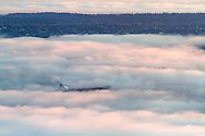 A Freighter anchored in Vancouver's English Bay surrounded by fog with Point Grey in the distance.  Photographed from the Cypress Lookout in Cypress Provincial Park in West Vancouver, British Columbia, Canada.